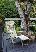 Rustic wooden lounger with cushions next to urns and tree on dark grey wooden deck