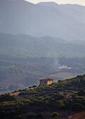 Isolated house on a hillside with view of Mediterranean mountain landscape