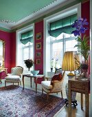 Rococo-style lounge chairs and side table in front of lattice windows with Roman blinds and deep pink walls in grand interior