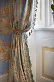 Draped curtain with small tassels in front of window in traditional, elegant interior