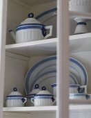 White and blue crockery on white cupboard shelves