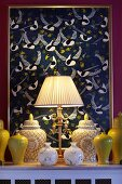 Table lamp with pale, pleated lampshade, collection of yellow ceramic vases and lidded jars in yellow and white in front of artwork with pattern of birds