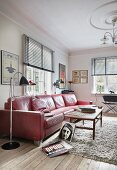 Standard lamp next to red, retro leather sofa and wooden coffee table on flokati rug in period living room with modern ambiance