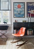 Charles Eames rocking chair with orange shell seat in front of floating sideboard below framed posters