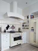 Vintage kitchen cooker flanked by modern, country-house-style, white cabinets with drawers below extractor hood in corner of kitchen