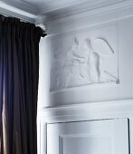 White, mythological low relief panel above traditional interior door with dark brown curtain to one side