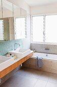 Modernes Bad mit Spiegelschrank über zwei Waschbecken neben Badewanne am Fenster