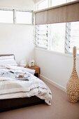 Bett mit gestreifter Bettwäsche in graubraunen Tönen in Schlafzimmerecke mit Fenster