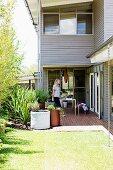 Sonnenbeschienener Garten mit Pflanzenkübeln vor mehrstöckigem Wohnhaus mit hellgrauer Holzfassade, Frau auf Terrasse