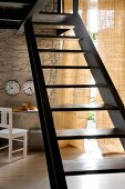 Metal staircase with wooden treads, airy curtain on terrace door and clocks on wall in rustic, designer interior