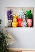 Photo of pineapples painted in bright colours on light grey wall with vintage lamp and palm leaves in foreground