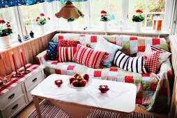 Comfortable seating area in loggia - white table, couch with patchwork throw against half-height wooden wall and potted red geraniums on windowsill