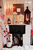 Red candles in candlestick and vintage lanterns on masonry stove