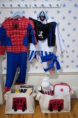 Spiderman and pirate dressing-up costumes hanging from coat pegs in child's bedroom