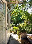 Wooden house encircled by paved path in sunny garden