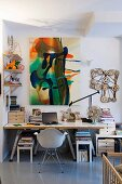 Contemporary painting and objets d'art in study with simple desk on trestles and classic shell chair