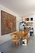 Large aboriginal artwork, dining table, bentwood chairs and colourful objects on kitchen shelves in background