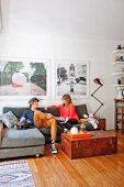 Young couple sitting on comfortable couch, wooden trunk on wooden floor and large photos on wall
