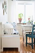 Rustic, white bench and table in front of potted plant on windowsill in simple dining room