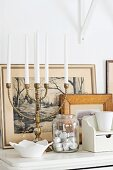 Multi-armed brass candelabra and jar of tealights in front of framed pictures on white shelf