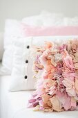 Scatter cushion with ruffles in shades of pink leaning against other cushions