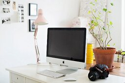 Computer, clip lamp and potted plant on white desk