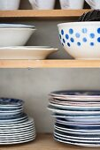 Stacked plates and bowls on wooden shelves
