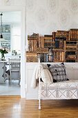 Vintage couch with white metal frame and lacy throw in front of stacked, antiquarian books on sideboard; view into dining room through open doorway to one side