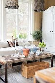 Rustic, DIY wooden coffee table and couch with pale cushions below window in rustic interior