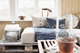 View across coffee table to couch made from wooden pallets and pale cushions below window