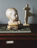 Stone bust of child on trivet
