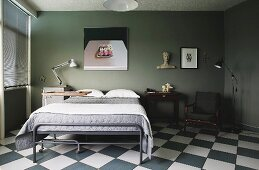 Vintage bed with grey metal frame below modern artwork on wall painted olive green in bedroom with chequered floor