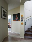 Artworks on painted foyer wall, foot of spiral staircase and view of young woman through open door in background