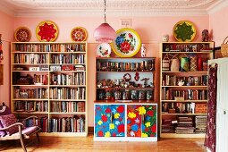 Library area with pink-painted walls and colourful floral dresser between full bookcases in collector's apartment