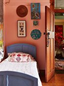 Wooden bed painted purple against pink wall with framed collection of butterflies and pictures next to open wooden door