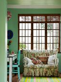 Comfortable sofa with vintage floral pattern below wooden lattice window and rug with bright green stripes in living area with green walls