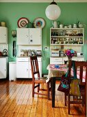 Wooden chairs around table on polished board floor in simple, functional kitchen with white cabinets against green-painted wall
