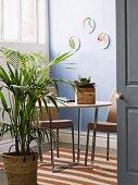 Blick durch offene Tür auf Palme im Topf vor Essplatz mit gepolsterten Stühlen um Tisch mit verchromtem Gestell in Zimmerecke