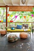 Roofed terrace with colourful bunting and pouffes in summery garden atmosphere