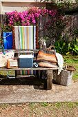 Beach bags on weathered bench in summery garden