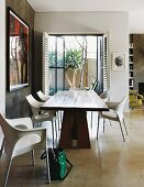 Solid wooden table and white designer chairs on pale concrete floor; open double doors leading to patio with palm trees