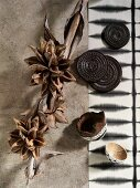 Dried seed pods and plants next to artistic, African wooden coasters and black and white batik runner