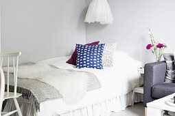 Scatter cushions and carefully selected blankets layered on bed - subtle grey and white interior with sparse accents of colour