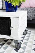 Simple, DIY coffee table on castors made from white-painted wooden blocks and boards with black-painted basket and deep blue glass vase