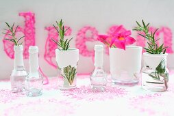 Sprigs of rosemary in small glass vessels dipped in white paint; pink string art picture in background