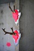 Zwei mit Neon-Pink bemalte Geweihschädel an Betonwand