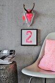In Neon-Pink bemalter Geweihschädel auf mit Blattsilber belegter Holzplatte und Typo-Bild an Betonwand