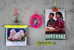 An Betonwand geklebte Kindermotivdrucke als Moodboard - Klemme und Kleiderbügel mit neonfarbenem Streifen, gehäkelter Rahmen um nostalgisches Kinderbild