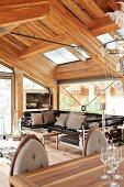 Offener Wohnraum mit Ledersofa in modernem Chalet mit sichtbarer Holz-Dachkonstruktion und Glasfronten
