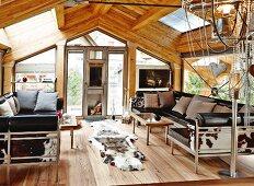 Loungebereich mit Ledersofagarnitur und Tierfellen im Dachgeschoss eines modernen Chalets